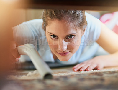 Buy stock photo Closeup shot of a young woman vacuuming underneath a piece of furniture