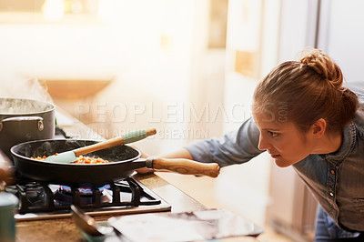 Buy stock photo Cropped shot of a young woman preparing a meal at home