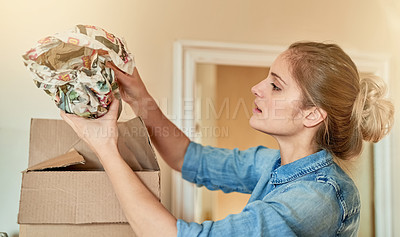 Buy stock photo Shot of a young woman unpacking a box at home