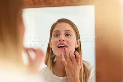 Buy stock photo Shot of a young woman touching up her lipstick in front of a mirror at home
