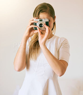 Buy stock photo Shot of an unrecognizable young woman taking a photo with her camera at home