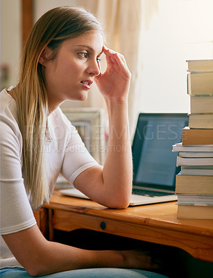 Buy stock photo Shot of a young woman looking overwhelmed by the pile of books on her desk