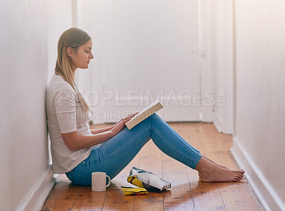 Buy stock photo Shot of a young woman reading a book while sitting on the floor at home