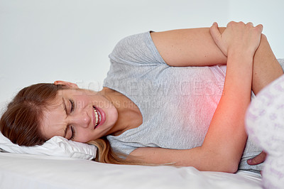 Buy stock photo Cropped shot of a young woman experiencing stomach pain highlighted in glowing red