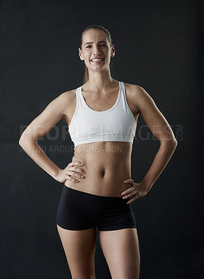 Buy stock photo Studio portrait of a sporty young woman standing against a dark background