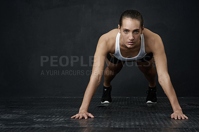 Buy stock photo Studio portrait of an attractive young woman working out against a dark background