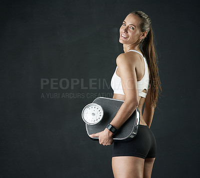 Buy stock photo Studio portrait of an attractive young woman holding a weightscale against a dark background