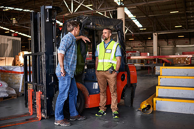 Buy stock photo Shot of two coworkers talking together by a florklift inside a large warehouse