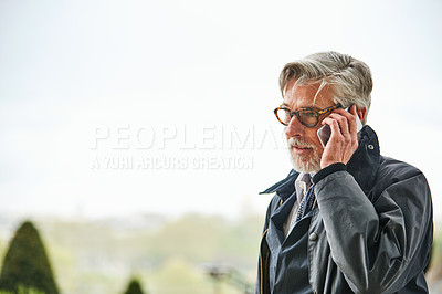 Buy stock photo Shot of a handsome mature man talking on a cellphone in the city
