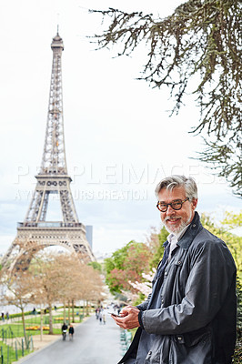 Buy stock photo Portrait of a handsome mature man using a cellphone in Paris with the Eiffel Tower in the background