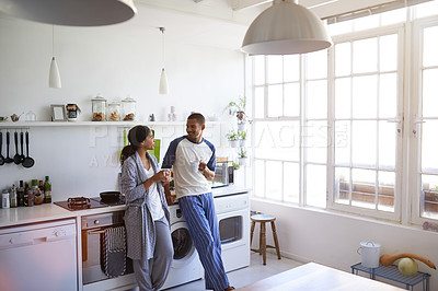 Buy stock photo Shot of a young couple talking and drinking coffee in the kitchen