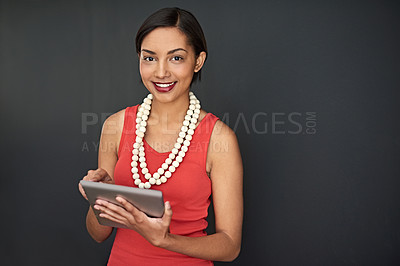 Buy stock photo Studio portrait of a young woman using a digital tablet against a gray background