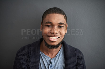 Buy stock photo Studio portrait of a smiling young man standing against a gray background