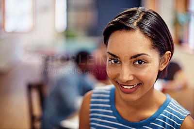 Buy stock photo Portrait of a smiling young woman standing in an office with colleagues working in the background