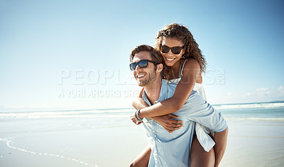 Buy stock photo Shot of a young man piggybacking his girlfriend on the beach