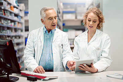 Buy stock photo Shot of two chemists at work in a pharmacy