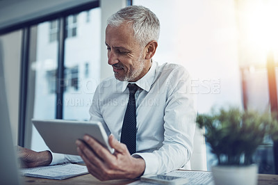 Buy stock photo Shot of a businessman sitting at his desk using a digital tablet