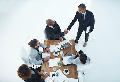 Buy stock photo Shot of two businesspeople shaking hands in a staff meeting