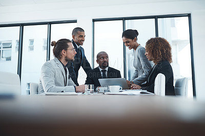 Buy stock photo Shot of a group of businesspeople discussing something on a laptop