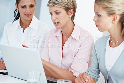 Buy stock photo Group of three confident businesswoman using laptop with colleagues at office - Teamwork
