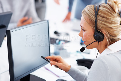 Buy stock photo Female call center employee working on a computer with headset - copyspace