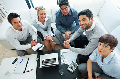 Buy stock photo High angle view of business people looking at you and smiling during meeting