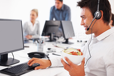 Buy stock photo Male call center employee holding bowl of fruits while working on computer with colleagues in background