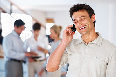 Buy stock photo Smiling business man using cellphone with colleagues in blurred background