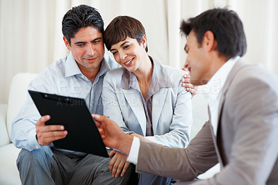 Buy stock photo Financial consultant advising couple with the help of document