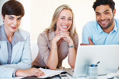Buy stock photo Portrait of an attractive business team sitting at table and smiling