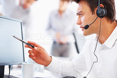 Buy stock photo Business man using headset and computer with colleagues in background