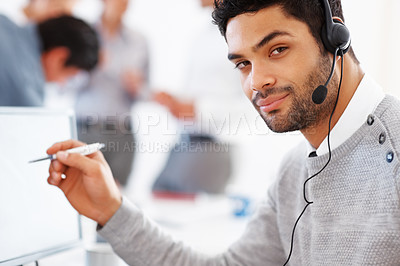 Buy stock photo Confident customer care executive holding pen with colleagues discussing in background
