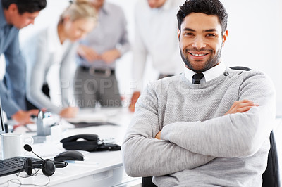 Buy stock photo Confident business man sitting in chair with colleagues discussing in background