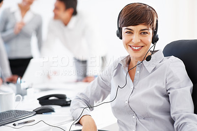 Buy stock photo Smiling customer care representative wearing headset with colleagues discussing in background