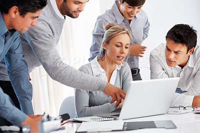 Buy stock photo Business man points at laptop screen while discussing with team