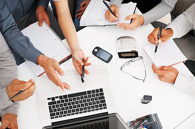 Buy stock photo High angle view of business people discussing work on laptop and taking notes