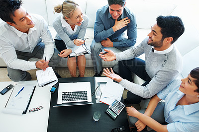 Buy stock photo High angle view of male executive and his colleagues discussing with laptop and documents on table