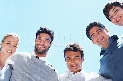 Buy stock photo Low angle view of smiling business people standing in huddle against sky - copyspace