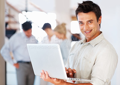 Buy stock photo Portrait of handsome business man using laptop and smiling with colleagues in background