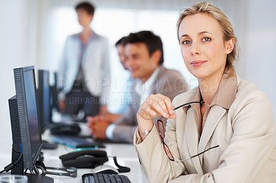 Buy stock photo Portrait of attractive business woman holding glasses and looking at you with co-workers in background