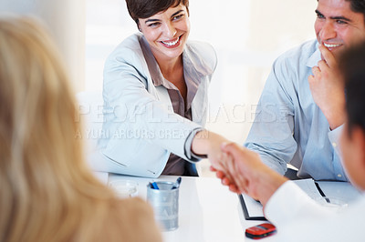 Buy stock photo Cute female executive smiling and shaking hands with male colleague during meeting
