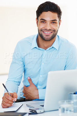 Buy stock photo Portrait of happy business man at his desk taking notes from laptop