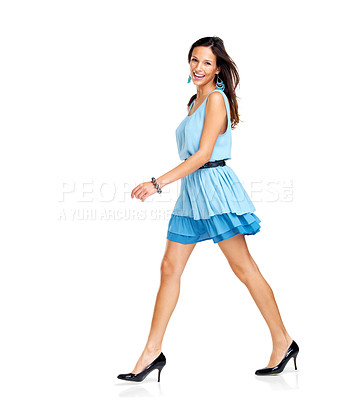 Buy stock photo Pretty young female model in blue dress walking on white background and smiling - Copysapce