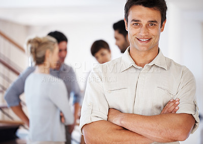 Buy stock photo Handsome business man with hands folded and colleagues discussing in background