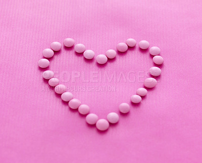Buy stock photo Sweet candies arranged in a heart shape on pink background