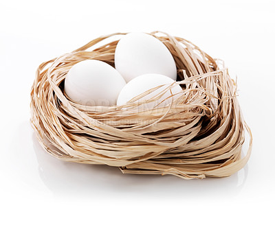 Buy stock photo Three chicken eggs in a small nest from a dry straw on a white background