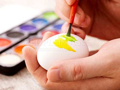 Buy stock photo Closeup human hand painting easter eggs with paintbrush in a bright colours