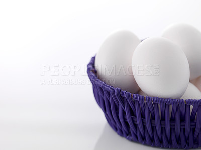 Buy stock photo Fresh eggs in a purple wicker basket isolated on white background with copyspace