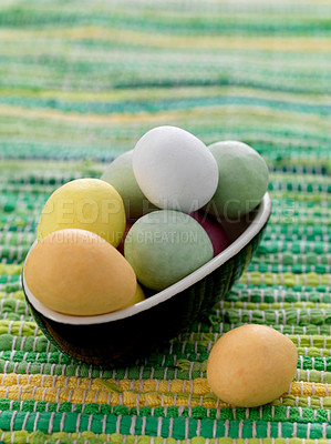 Buy stock photo Bowl full of easter colored chocolate eggs on carpet