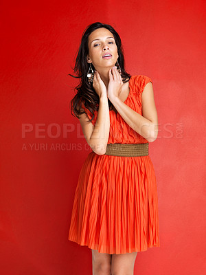Buy stock photo Portrait of glamorous young female model posing confidently against red background